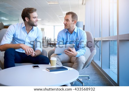 smiling business partners sitting in a bright modern office space talking positively and using a bright modern office space