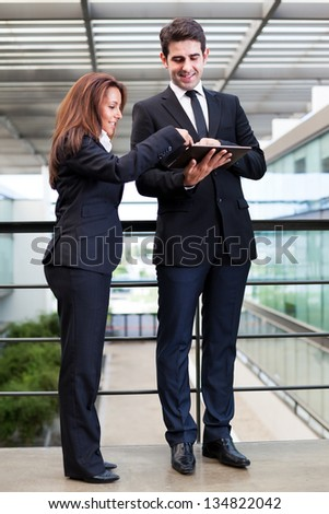 Smiling business partners working with electronic tablet at modern office bulding