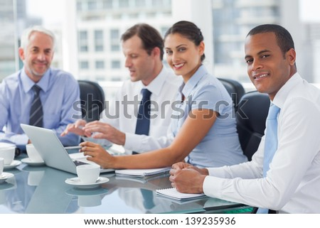 Smiling business people brainstorming  in the meeting room - stock photo