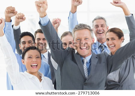Smiling business people cheering in office - stock photo