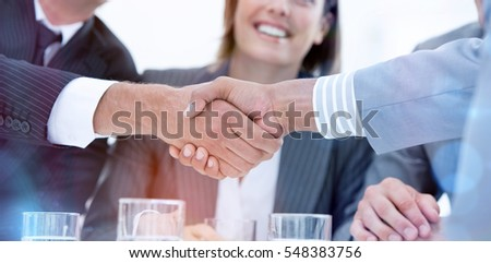 Smiling business people closing a deal against a white background