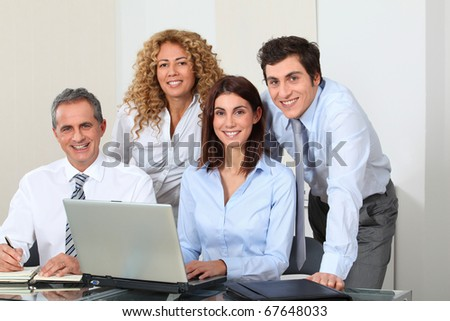 Smiling business people meeting in office - stock photo