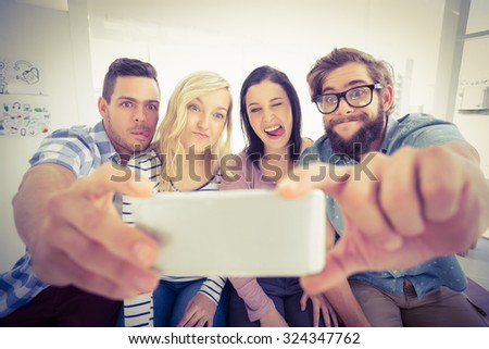 Smiling business people posing for selfie while sitting on desk in office - stock photo