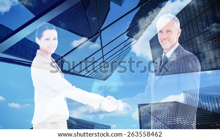 Smiling business people shaking hands while looking at the camera against skyscraper - stock photo