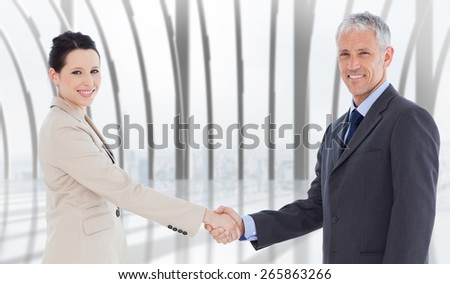 Smiling business people shaking hands while looking at the camera against white room with large window overlooking city - stock photo
