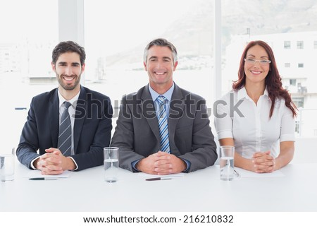 Smiling business people sitting together in an office - stock photo