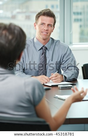 Smiling business people talking on business meeting. Over the shoulder view. - stock photo