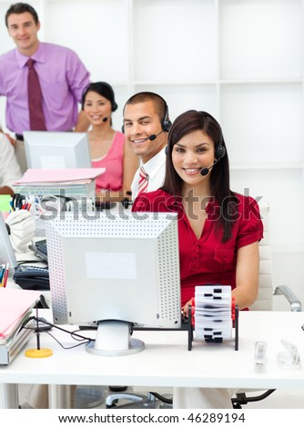 Smiling business people with headset on working in the office - stock photo
