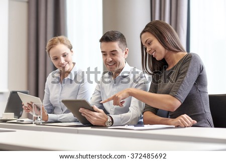 smiling business people with tablet pc in office - stock photo