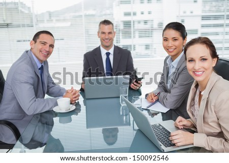 Smiling business people working together with their laptop in bright office - stock photo