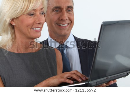 Smiling business professionals looking at a laptop - stock photo