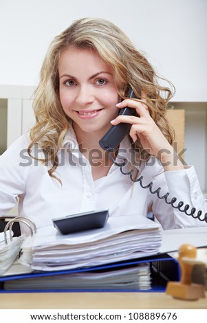 Smiling business secretary on the phone in her office - stock photo