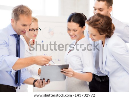smiling business team discussing something in office - stock photo