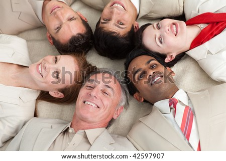 Smiling business team lying in a circle with heads together - stock photo