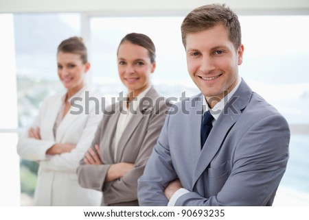 Smiling business team standing with arms folded - stock photo