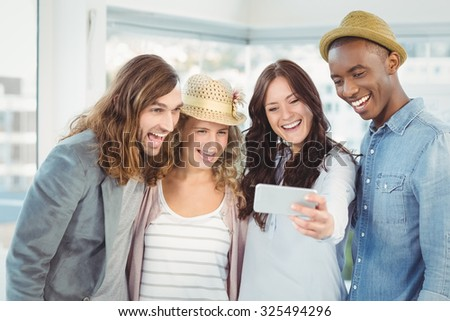 Smiling business team taking selfie while standing at office - stock photo