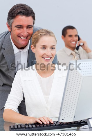 Smiling business team working at a computer in the office - stock photo