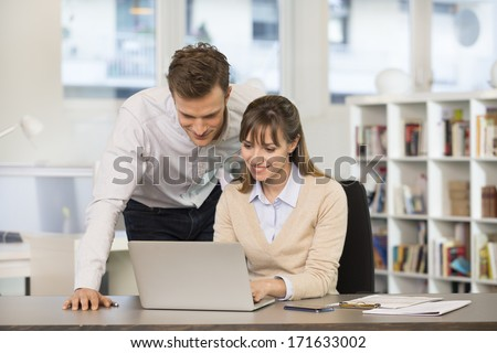 Smiling business team working on computer in office - stock photo