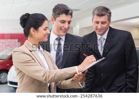 Smiling business team working together on clipboard at new car showroom - stock photo