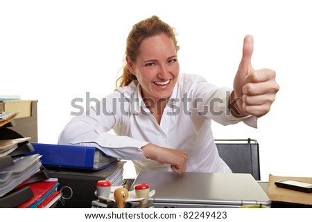 Smiling business woman at her desk holding thumbs up - stock photo