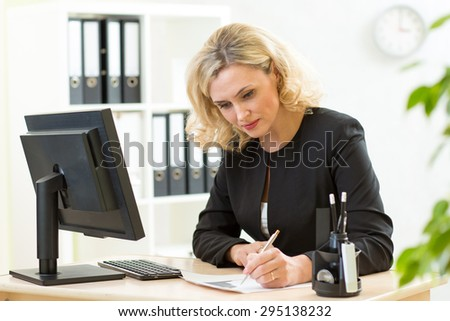 smiling business woman filling in documents with pen - stock photo