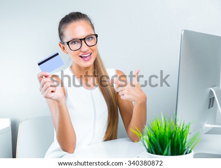 smiling business woman holding credit card and pointing her finger on it. busy woman working on personal computer. money - stock photo