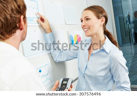 Smiling business woman in a team workshop pointing to financial graph - stock photo