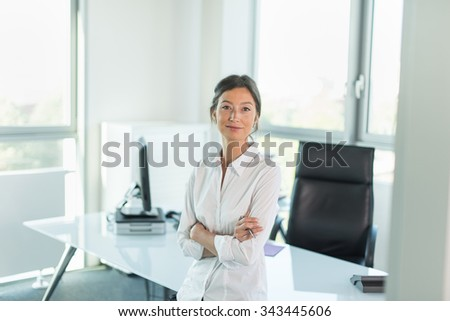 Smiling business woman in her 30's leaning against her glass desk in her white, luminous office. She is wearing a white shirt and dark pants, her hair are tied. She is looking at camera