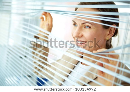 Smiling business woman looking out of the window with blinds - stock photo