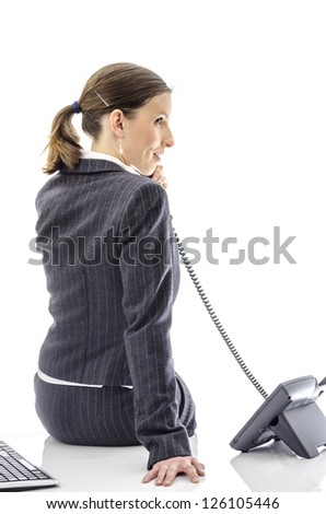 Smiling business woman sitting on a white office desk talking on a telephone.
