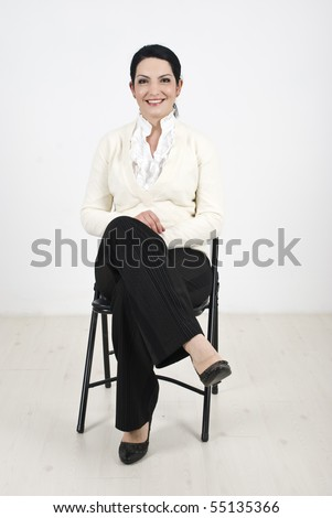 Smiling business woman sitting on chair and waiting something - stock photo