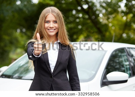 Smiling business woman standing in front of car and makes gesture with thumb up