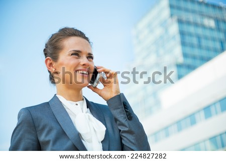 Smiling business woman talking mobile phone in front of office building - stock photo