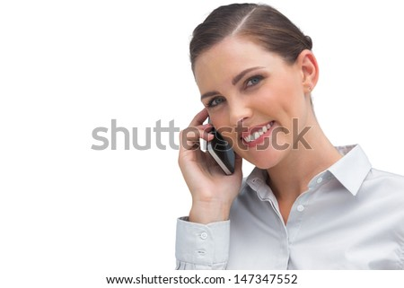 Smiling business woman talking on mobile phone and looking at the camera