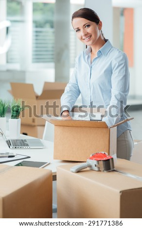 Smiling business woman unpacking a cardboard box in her new office on her desk, new job and relocation concept - stock photo