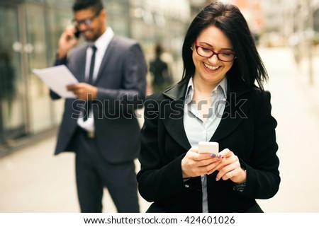 Smiling business woman using smart phone in front of the office - stock photo