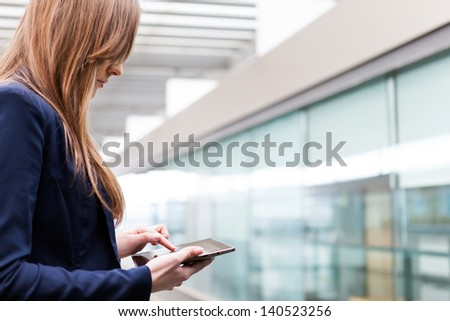 Smiling business woman using tablet PC at the office - stock photo