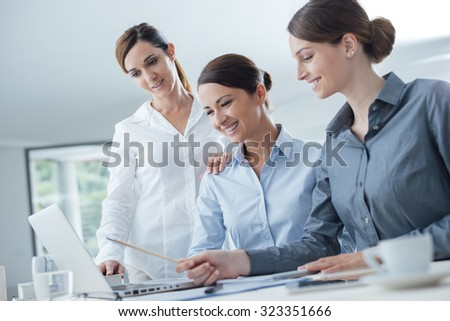 Smiling business women team working at office desk and discussing a project on a laptop