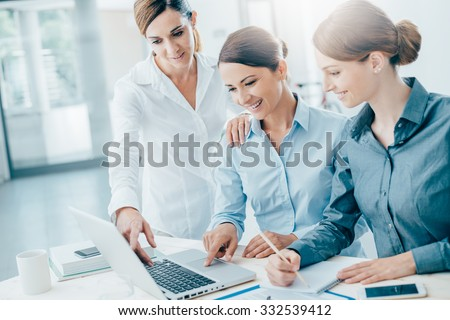 Smiling business women team working at office desk and discussing a project on a laptop - stock photo