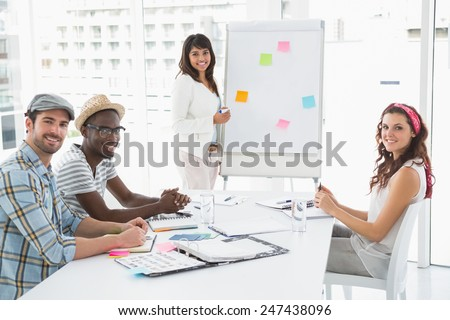 Smiling businessman and colleagues looking at camera in the office - stock photo