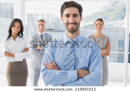 Smiling businessman and his co-workers standing behind - stock photo