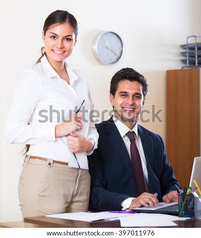 Smiling businessman and his young attractive secretary working in modern office 