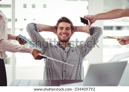 Smiling businessman being handed items in casual office