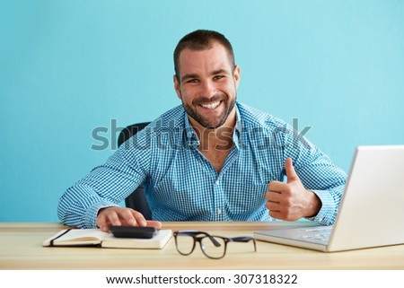 Smiling businessman calculates taxes and gesturing thumbs up - stock photo