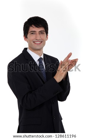 Smiling businessman clapping his hands - stock photo