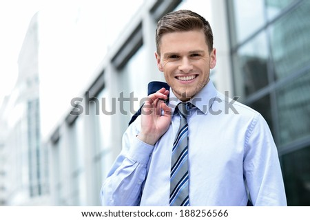 Smiling businessman, coat slung over his shoulder - stock photo
