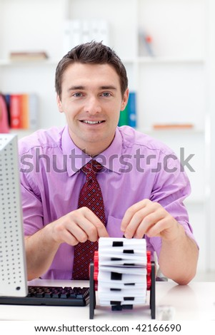 Smiling businessman consulting his business card holder in the office - stock photo