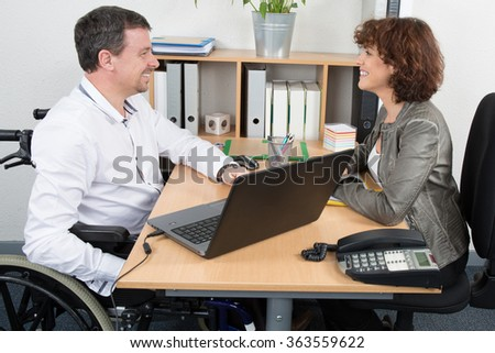 Smiling businessman disabled interviewing candidate in an office
