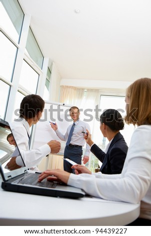 Smiling businessman discussing business project with his employees - stock photo
