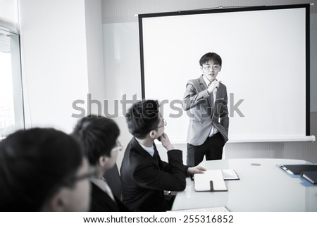 Smiling businessman discussing plans with his colleagues in board meeting.asian - stock photo
